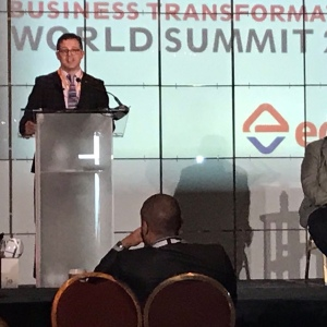 Ian Hawkins standing behind podium at business transformation world summit