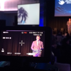 Ian Hawkins presenting from dark stage, seen through viewfinder of a camera
